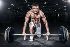 Athletic shirtless young sports man - fitness model holds the barbell in gym. Copy space fore your text. Athletic shirtless young sports man - fitness model stock photography