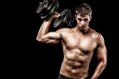 Athletic shirtless young sports man - fitness model holds the dumbbell in gym. Copy space fore your text. Stock Image