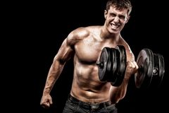 Athletic shirtless young sports man - fitness model holds the dumbbell in gym. Copy space fore your text. Athletic shirtless young sports man - fitness model Stock Images