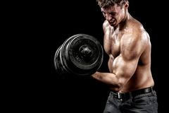 Athletic shirtless young sports man - fitness model holds the dumbbell in gym. Copy space fore your text. Athletic shirtless young sports man - fitness model Stock Photo