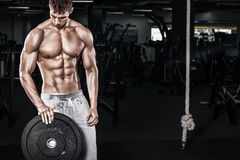 Athletic shirtless young sports man - fitness model holds the dumbbell in gym. Copy space fore your text. Athletic shirtless young sports man - fitness model Royalty Free Stock Photography