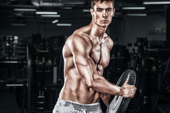 Athletic shirtless young sports man - fitness model holds the dumbbell in gym. Copy space fore your text. Athletic shirtless young sports man - fitness model Royalty Free Stock Photos