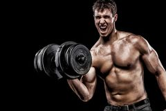 Athletic shirtless young sports man - fitness model holds the dumbbell in gym. Copy space fore your text. Athletic shirtless young sports man - fitness model Stock Photos
