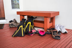 Athletic shoes, sandals, swim fins at vacation home Stock Photo