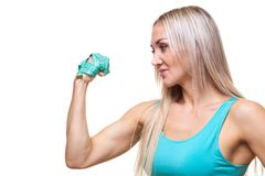 Athletic slender woman holding a measuring tape in the fist of her hand. The concept of will power, purposefulness. Royalty Free Stock Image