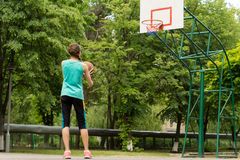 Athletic slender young girl playing basketball Royalty Free Stock Images
