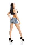 Athletic, slim girl in denim shorts and a sports bodice isolated Royalty Free Stock Images