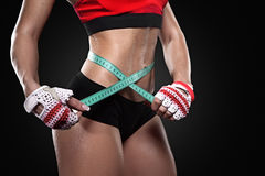 Athletic slim woman measuring her waist by measure tape Royalty Free Stock Photography