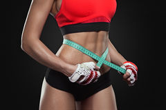 Athletic slim woman measuring her waist by measure tape Stock Photo