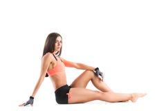 Athletic slim woman in sportswear sitting. Royalty Free Stock Image