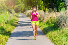 Athletic smiling woman running outdoors. Sporty young woman runs on track through nice nature being happy Stock Images