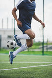 Athletic soccer player training with ball on soccer pitch Royalty Free Stock Image