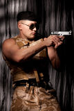 Athletic soldier aiming with handgun Royalty Free Stock Image