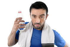 Athletic sport man  holding water bottle wiping out sweat after Royalty Free Stock Image