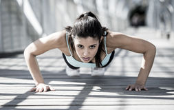Athletic sport woman doing push up before running in urban training workout. Young beautiful and athletic sport woman doing push up before running in urban Royalty Free Stock Images