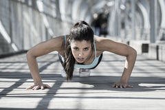 Athletic sport woman doing push up before running in urban training workout royalty free stock photography