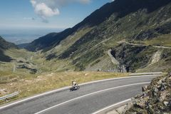 Professional cyclist rides winding road stock photography