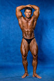 Athletic sports bodybuilder demonstrates posture Royalty Free Stock Photo
