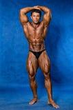 Athletic sports bodybuilder demonstrates posture Royalty Free Stock Image