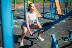Athletic sports young woman doing exercises on sports field with simulators stock image