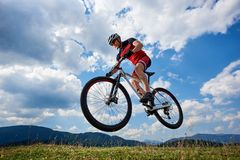 Athletic sportsman cyclist in professional sportswear and helmet flying in air on his bicycle royalty free stock images
