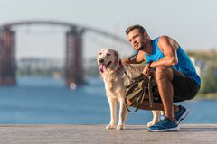 Sportswoman with dog on quay. Athletic sportsman hugging golden retriever dog on quay Royalty Free Stock Images