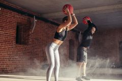 Athletic young man and woman in sportswear exercising with medicine balls in gym stock images