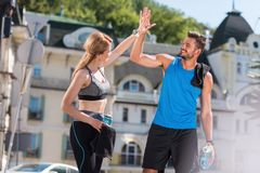 Sportswoman and sportsman giving highfive. Athletic sportswoman and sportsman giving highfive in city at daytime Stock Images