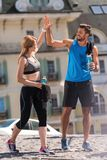 Sports couple. Athletic sportswoman and sportsman jogging in city at daytime Stock Photo