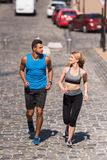 Sportswoman and sportsman jogging in city Royalty Free Stock Photography