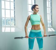 An athletic, sporty female dressed in an azure sportswear holds barbell. An athletic, sporty female dressed in an azure sportswear holds barbell and posing near Royalty Free Stock Photography