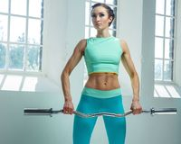 An athletic, sporty female dressed in an azure sportswear holds barbell. An athletic, sporty female dressed in an azure sportswear holds barbell and posing near Royalty Free Stock Image