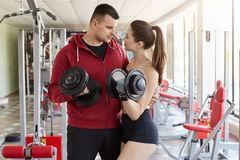 Athletic sporty guy hugs, gives little cuddle to beautiful slim young lady, looks in her eyes attentively. Sporty couple holds. Dumbbills in their hands royalty free stock images
