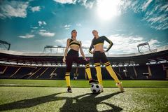 Two athletic sporty women from one team in sportswear with soccer ball on stadium. stock image