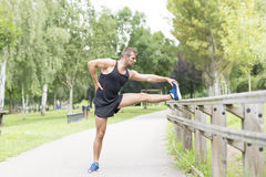 Athletic strong man doing stretches before exercising, outdoor. stock photography