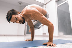 Athletic strong man practicing difficult yoga pose. Royalty Free Stock Image