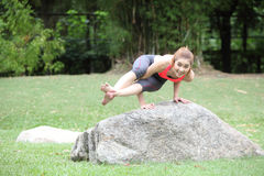 Athletic strong woman practicing difficult yoga pose outdoors. Photo of  Athletic strong woman practicing difficult yoga pose outdoors Stock Photos