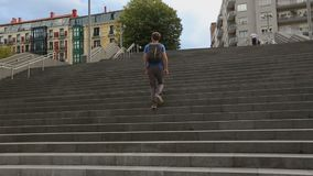 Athletic student running up granitic stairs, late for class at university. Stock footage stock video