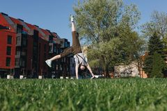athletic stylish young woman doing side somersault on grass royalty free stock photos