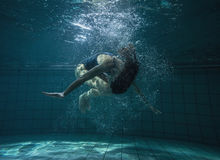 Athletic swimmer doing a somersault underwater Stock Photo