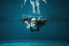 Athletic swimmer smiling at camera underwater Royalty Free Stock Photography