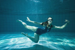 Athletic swimmer smiling at camera underwater Stock Image