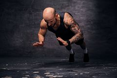 Sporty shaved head sporty male doing push ups with jumps. stock photo