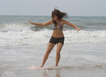 Athletic teen girl skim boarding at the beach stock photos