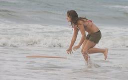 Athletic teen girl throwing a board into the ocean. Athletic teen girl throwing a skim board into the Atlantic Ocean in Emerald Isle, North Carolina Stock Photo