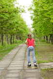 Athletic teenage girl roller skating in a park Royalty Free Stock Photo
