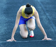 Athletic teenage girl in start position . Royalty Free Stock Photos