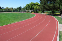 Athletic Track. Curving Around Green Grass Field Stock Photos