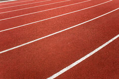 Athletic Track Lanes Angle. Athletics track lanes with the first twenty meters of white marked track lanes in horizontal photo image frame.Low angle view of Stock Photography