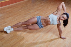 Athletic trainer. Beautiful athletic trainer shows examples of exercises in the gym Royalty Free Stock Photo